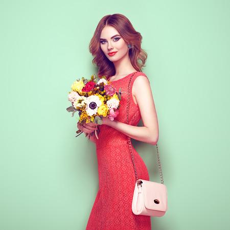 エレガントな赤いドレスで金髪の若い女性。ハンドバッグと緑の背景にポーズの女の子。宝石と髪型。春の花の花束を持つ女性。ファッション写真 写真素材