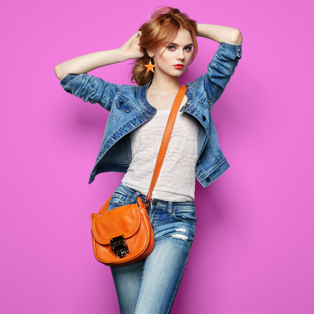 Fashion portrait of beautiful young woman with red hair. Girl in blouse and jeans. Jewelry and hairstyle. Girl with handbag