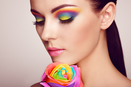 Portrait of beautiful young woman with rainbow rose. Bright colors. Long eyelashes, vivid colorful eyeshadows. Rainbow make up. Multicolored flowers Stock Photo