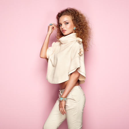Fashion portrait of woman in summer outfit. Girl posing on pink background. Stylish curly hairstyle. Glamour lady