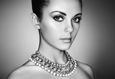 Portrait of young beautiful woman with perfect makeup. Face Girl with necklace close up. Fashion jewelry. Black and White photo
