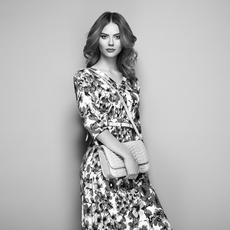 Blonde young woman in floral spring summer dress. Summer floral outfit. Stylish wavy hairstyle. Fashion photo. Glamour lady with handbag. Black and White photo photo