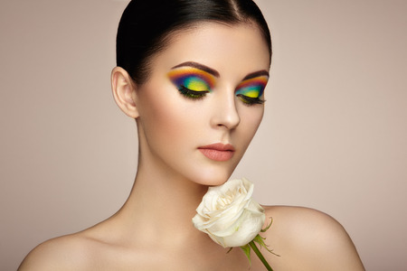 Portrait of beautiful young woman with rainbow make-up. Girl summer. Long eyelashes, vivid colorful eyeshadows. White rose. Multicolored Banco de Imagens