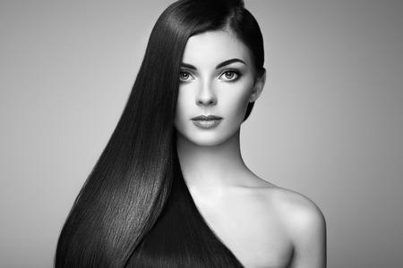 긴 부드러운 머리를 가진 아름 다운 여자입니다. 완벽 한 메이크업을 가진 소녀입니다. 완벽한 건강한 검은 머리와 모델 갈색 머리. 흑백 사진 스톡 콘텐츠