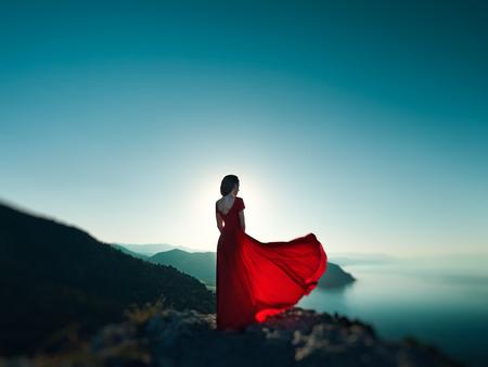 Jonge mooie vrouw in rode jurk op zoek naar de bergen zee. Meisje op de aard op blauwe hemel achtergrond. Mode foto