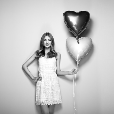heartshaped: Beautiful young woman with heart shape air balloon. Woman on Valentines Day. Symbol of love. Black and White photo