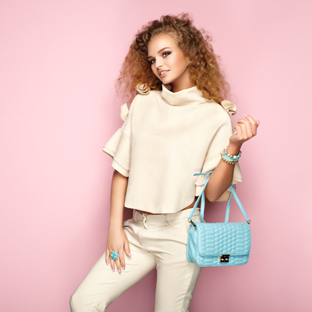 Fashion portrait of woman in summer outfit. Girl posing on pink background. Blue handbag. Stylish curly hairstyle. Glamour lady