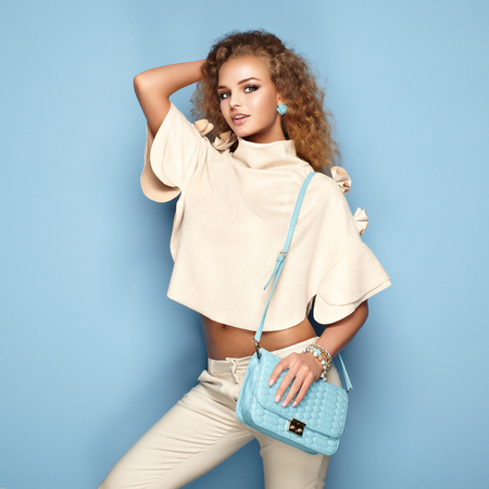 Fashion portrait of woman in summer outfit. Girl posing on blue background. Blue handbag. Stylish curly hairstyle. Glamour lady