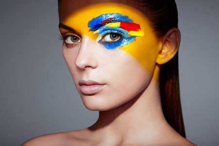 Fashion model woman with colored face painted. Beauty fashion art portrait of beautiful woman with colorful abstract makeup. Face painted paints. Multicolor design