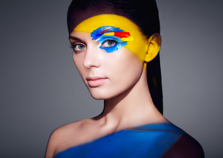 Fashion model woman with colored face painted. Beauty fashion art portrait of beautiful woman with colorful abstract makeup. Face painted paints. Multicolor design photo