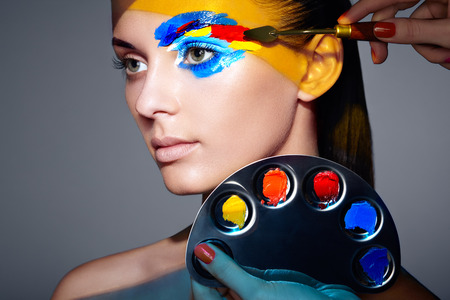 Makeup artist applies colorful makeup. Fashion model woman with colored face painted. Beauty art portrait of beautiful model with colorful abstract makeup photo