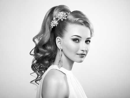 hairdresser: Fashion portrait of young beautiful woman with jewelry and elegant hairstyle. Blonde girl with long wavy hair. Perfect make-up.  Black and white photo Stock Photo