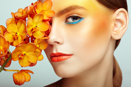 Portrait of beautiful young woman with orchid. Brunette woman with luxury makeup. Perfect skin. Eyelashes. Cosmetic eyeshadow. Orange flowers Stock Photo
