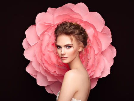 Hermosa mujer en el fondo de una flor grande. Belleza chica modelo de verano con peonía rosa. Mujer joven con peinado elegante y maquillaje. Foto de moda