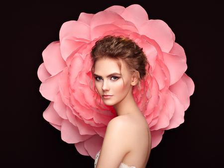 Mooie vrouw op de achtergrond van een grote bloem. Schoonheid zomermodel meisje met roze pioen. Jonge vrouw met elegant kapsel en make-up. Mode foto