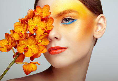 Portrait of beautiful young woman with orchid. Brunette woman with luxury makeup. Perfect skin. Eyelashes. Cosmetic eyeshadow. Orange flowers Foto de archivo