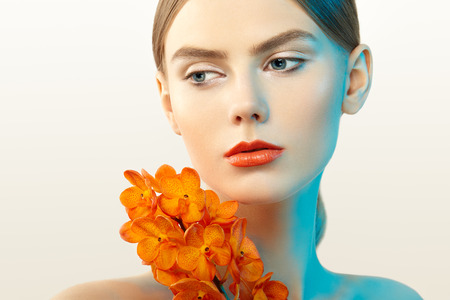 gloss: Portrait of beautiful young woman with orchid. Brunette woman with luxury makeup. Perfect skin. Eyelashes. Cosmetic eyeshadow. Orange flowers Stock Photo