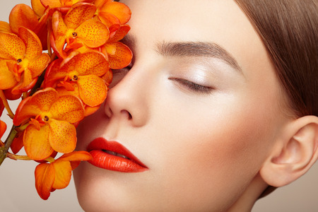 Portrait of beautiful young woman with orchid. Brunette woman with luxury makeup. Perfect skin. Eyelashes. Cosmetic eyeshadow. Orange flowers Фото со стока