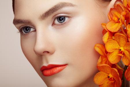 Portret van mooie jonge vrouw met orchidee. Brunette vrouw met luxe make-up. Perfecte huid. Wimpers. Kosmetische oogschaduw. Oranje bloemen Stockfoto