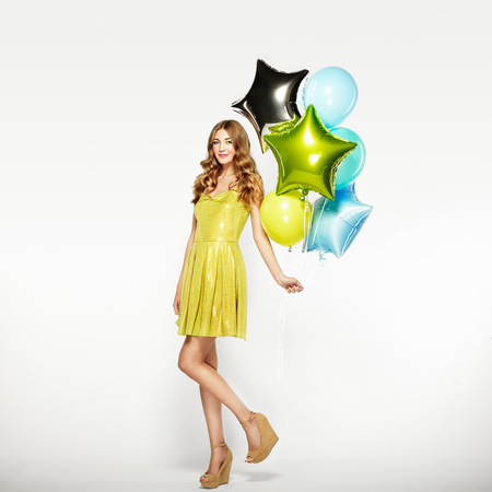 christmas gift: Beautiful young woman with colorful balloons on a white background. Birthday and party. Girl in green dress at the festival