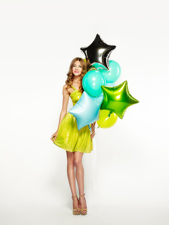 Beautiful young woman with colorful balloons on a white background. Birthday and party. Girl in green dress at the festival