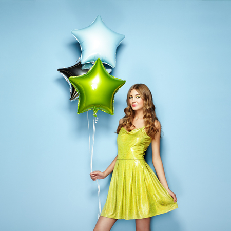 christmas gift: Beautiful young woman with colorful balloons on a blue background. Birthday and party. Girl in green dress at the festival Stock Photo