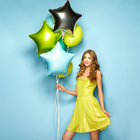 Beautiful young woman with colorful balloons on a blue background. Birthday and party. Girl in green dress at the festival Stock Photo