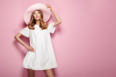 Blonde Young Woman in elegant white Dress and Summer Hat. Girl posing on a Pink Background. Jewelry and Clothing. Fashion photo