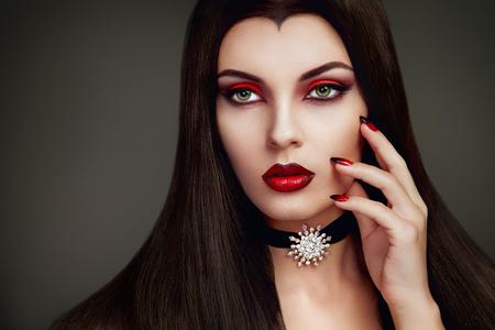 ハロウィン吸血鬼の女性の肖像画。美しいグラマー ファッションでセクシーなヴァンパイア女性長い黒髪、美メイクし、衣装 写真素材