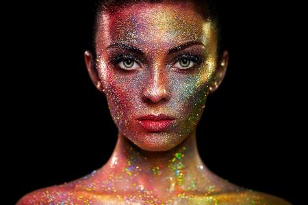 彼女の顔の上で輝きと美しい女性の肖像画。色光のアート メイクの女の子。カラフルなメイクとファッション モデル