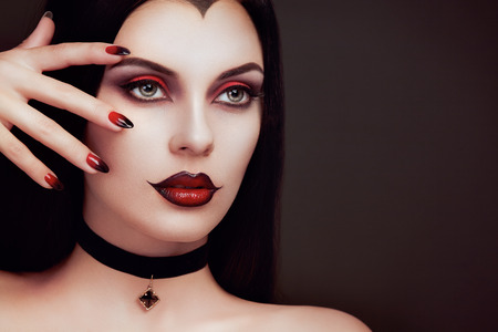 Halloween Vampire Woman portrait. Beautiful Glamour Fashion Sexy Vampire Lady with long dark Hair, beauty make up and Costume Imagens - 88453049
