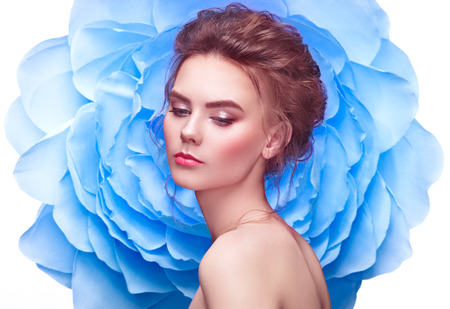 Beautiful Woman on the Background of a Large Flower. Beauty Summer Model Girl with Blue Peony. Young Woman with elegant Hairstyle and Makeup. Fashion Photo Stock Photo