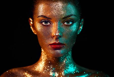 Portrait der schönen Frau mit Scheinen auf ihrem Gesicht. Mädchen mit Kunst-Make-up im Farblicht. Mode-Modell mit buntem Make-up