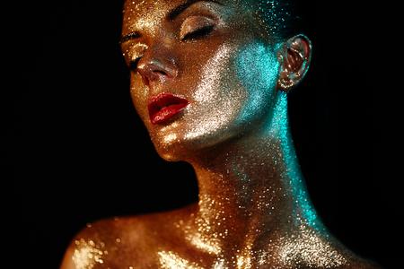 Portret van mooie vrouw met fonkelingen op haar gezicht. Meisje met kunst make-up in kleurenlicht. Mannequin met kleurrijke make-up
