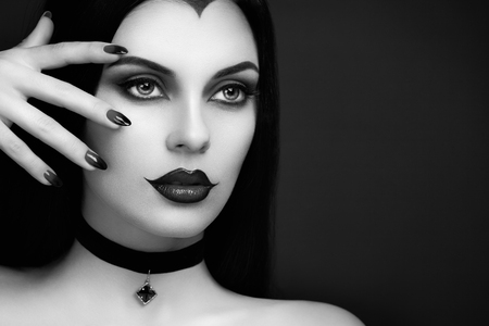 Halloween Vampire Woman portrait. Beautiful Glamour Fashion Sexy Vampire Lady with Long Dark Hair, Beauty Make Up and Costume Imagens