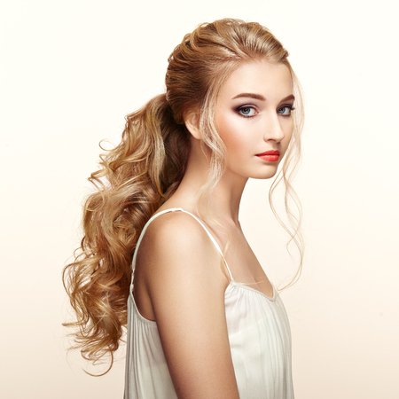 Blonde Girl with Long and shiny Curly Hair. Beautiful Model Woman with Curly Hairstyle. Care and Beauty Hair products. Perfect Make-Up