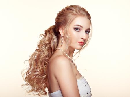 Blond meisje met lang en glanzend krullend haar. Mooie modelvrouw met krullend kapsel. Verzorging en schoonheid Haarproducten. Perfecte make-up en sieraden Stockfoto