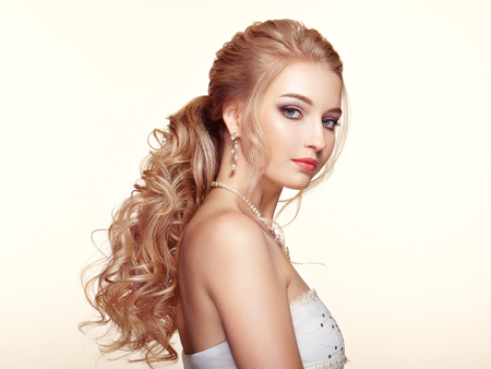 Blonde Girl with Long and shiny Curly Hair. Beautiful Model Woman with Curly Hairstyle. Care and Beauty Hair products. Perfect Make-Up and Jewelry