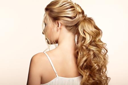 길고 반짝이는 곱슬 머리를 가진 금발 소녀. 아름 다운 모델 여자 곱슬 헤어 스타일입니다. 케어 및 뷰티 헤어 제품. 머리카락 관리 및 미용 스톡 콘텐츠