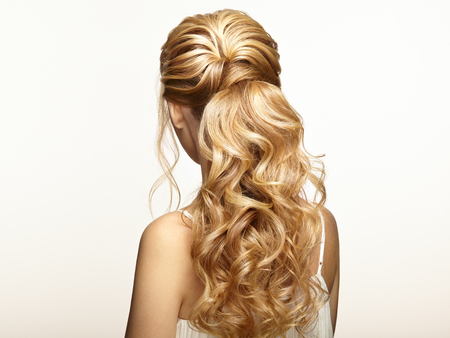 Blond meisje met lang en glanzend krullend haar. Mooie modelvrouw met krullend kapsel. Verzorging en schoonheid Haarproducten. Zorg en schoonheid van haar