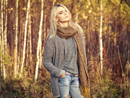 Portrait of Young beautiful woman in autumn pullover. Fashion photo. Blonde girl. Perfect make-up