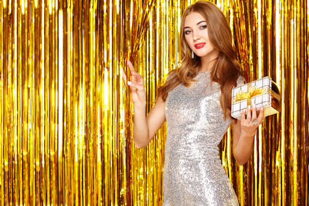 Beautiful Woman celebrating New Year and Christmas. Girl with Box of Gifts. Girl posing over Golden sparkly background. Happy New Year. Holiday and Party