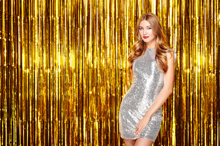 Beautiful Woman celebrating New Year and Christmas. Girl in glamorous Silver Dress. Girl posing over Golden sparkly background. Happy New Year. Holiday and Party Stock Photo