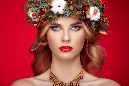 Portrait of beautiful young woman with Christmas wreath. Beautiful New Year and Christmas tree holiday hairstyle and makeup. Beauty girl portrait isolated on red background. Colorful makeup and hair