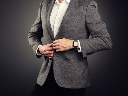 d68fa78af38 Handsome Young Man in Business Suit. Casual Style and Electronic Gadgets.  Smart Watch