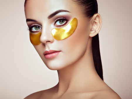 Portret van schoonheidsvrouw met ooglapjes. Vrouw schoonheid gezicht met masker onder de ogen. Mooie vrouw met natuurlijke make-up en gouden cosmetica collageenpleisters op frisse gezichtshuid Stockfoto