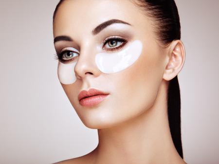 Retrato da mulher da beleza com remendos do olho. Rosto de beleza de mulher com máscara sob os olhos. Mulher bonita com maquiagem natural e manchas de colágeno branco cosméticos na pele facial fresca