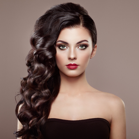Brunette Woman with Curly Hairstyle. Beautiful Girl with long Wavy Hair. Perfect Makeup. Fashion photo Stok Fotoğraf