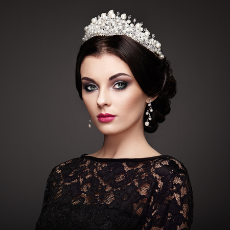 Fashion Portrait of Beautiful Woman with Tiara on head. Elegant Hairstyle. Perfect Make-Up and Jewelry. Red Lips Banco de Imagens