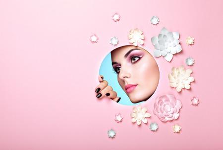 Retrato conceptual da beleza da mulher nova bonita. Rosto de menina com maquiagem de primavera rosa. Beleza moda modelo mulher rosto pele perfeita. Flores de papel no fundo rosa